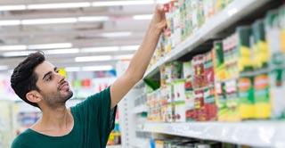 Comparando en el supermercado diferentes marcas de fruta confitada sin conservantes ni colorantes artificiales en el supermercado.