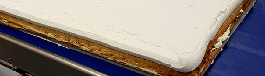 Preparación de una plancha de hojaldre con geles para tartas de Lazaya en una pastelería industrial.