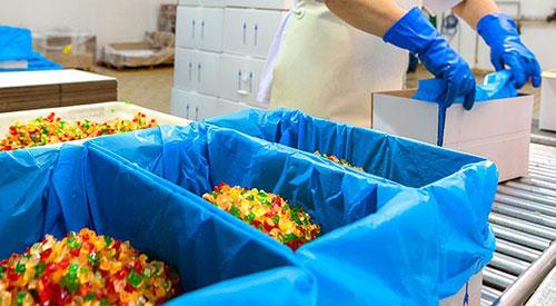 Empaquetando cubitos de fruta confitada en cajas con bolsa.