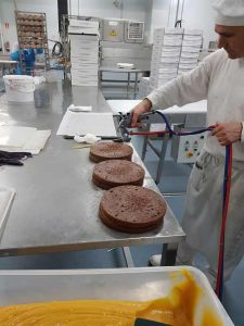Application of sugar syrup on sacher cake filled with apricot jam