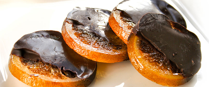Orange slices with dark chocolate recently made.