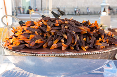 Candied orange peel covered in chocolate in a silver plated dish on the table.