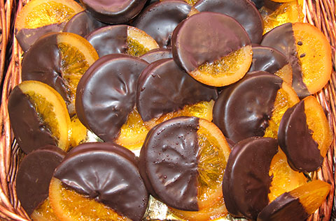 Artisan confectionery with candied orange slices dipped in dark chocolate.